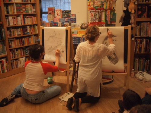 "Melissa Guion and Sophie Blackall drawing the word, ""battle"""