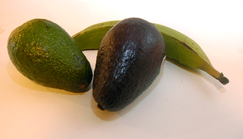 An unripened avocado and a ripe one, with an unripened plantain cozying up to them.  The ripened bananas were cut up and frozen.